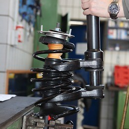 Compress the suspension spring using a spring tensioner
